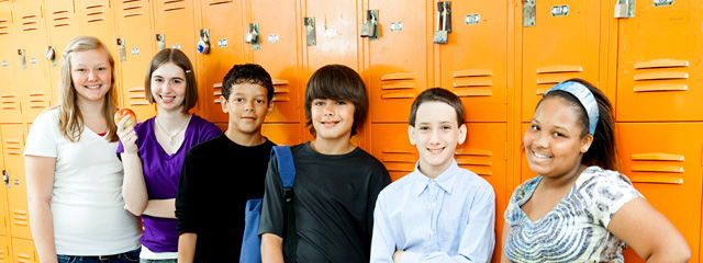 A group of kids stand outside lockers.