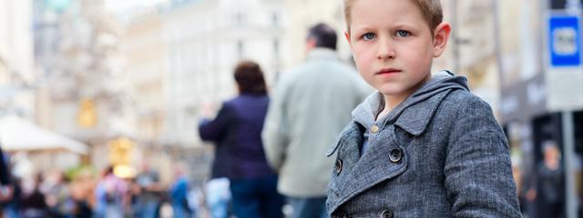 A child walks alone on a city street.