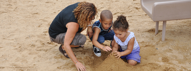 How to Guide Your Toddler's Emotional Development | The ultimate goal in raising a child is independence, and that goal is the same in guiding your toddler's emotional development. | Two toddlers play with their mother in the sand.