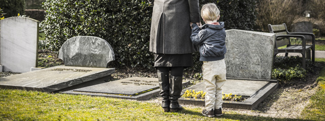 A young boy stands with his mother at a cemetery, looking at a headstone.