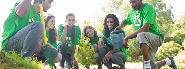 A group of teens cleans up a park and plants bushes for Earth Day.