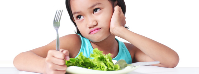 A young girl makes a pouty face in front of her salad.