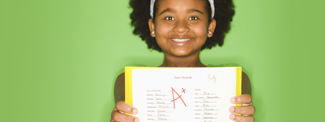 A young girl smiles proudly as she shows her A+ test score.