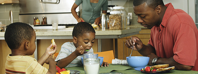 Breakfast + Dinner: A Student's Meal Ticket to Success | Your child can't focus or succeed in school if they're hungry. Be sure that they have a healthy breakfast to help them focus in class and a healthy dinner to help them sleep so they're rested the next morning. | A family eats breakfast in the morning.