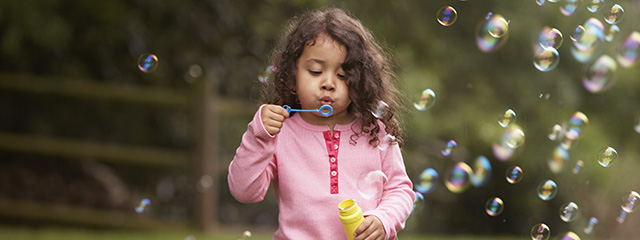 Reflect + Reenergize with These Back to School Activities | Regroup and gather your thoughts and emotions before the school year starts with your family with these 4 activities. | A girl blows bubbles in the park.