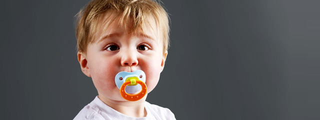 Bye-Bye Binky! | A toddler sits with his pacifier in his mouth, looking innocent and curious.
