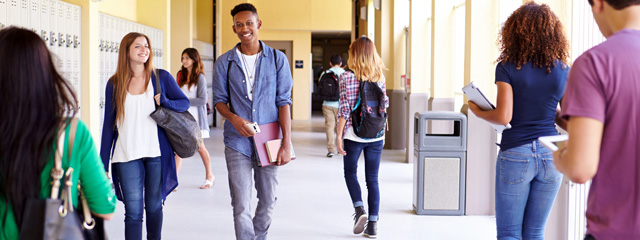 5 Steps to Start Freshman Year Right | High school students walk through the hallway at school.