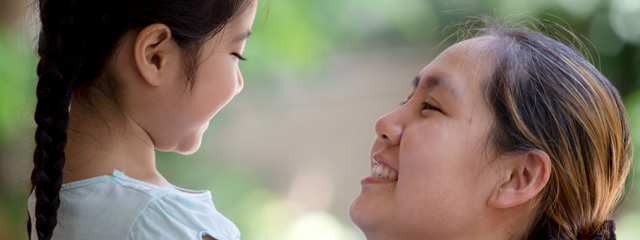 My Story: Learning to Express Love To Your Children | A mother holds her smiling daughter and looks lovingly into her eyes.