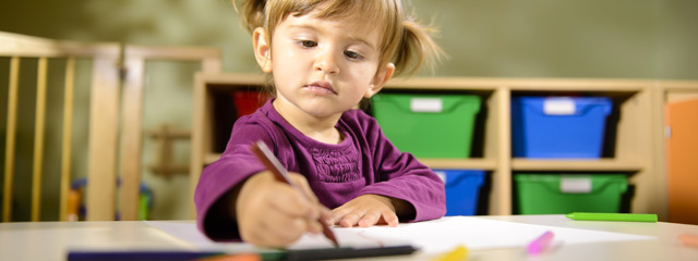 Prepare for Kindergarten in 8 Steps | A young girl sits in a preschool classroom drawing on paper.