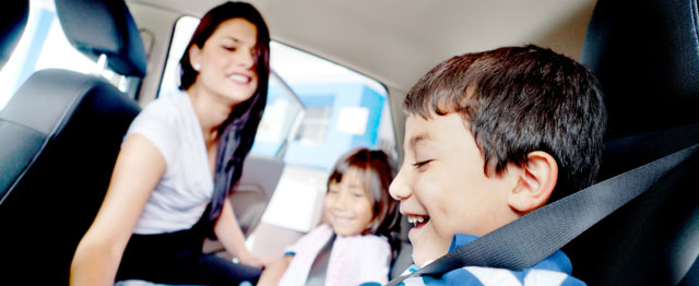 Paisanos: 3 Tips To Help Your Child During the Holidays | A mother buckles her children into the backseat of the car.
