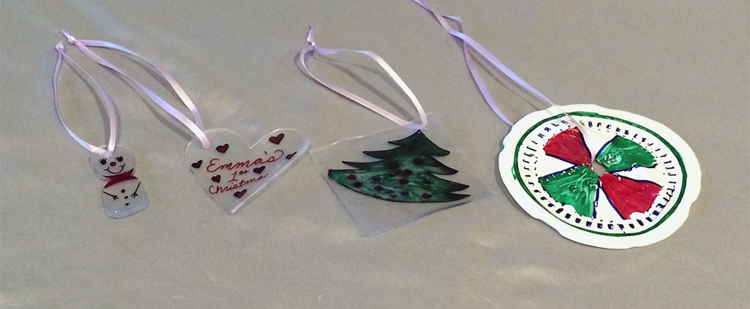"DIY: Shrinky Dink Repurposed Plastic Ornaments + Jewelry | 4 shrinky dink ornaments, a snowman, a Christmas tree, a red and green wheel, and a heart with the words ""Emma's 1st Christmas."""