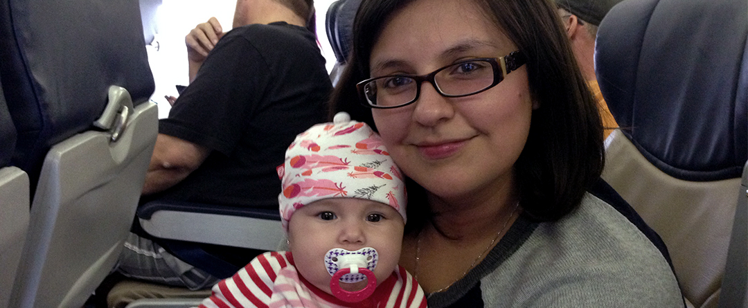 Tips for Traveling with an Infant | The author sits on the plane with her infant in her lap.