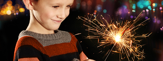 Throw a kid-friendly New Year's Eve Bash | There's no need for a sitter if you're hosting a New Year's Eve bash that both kids and adults will love. The key is to provide food, drinks, games, and music that all ages can enjoy. | A child smiles as he holds a sparkler on New Year's Eve.