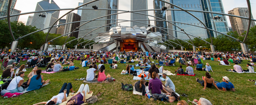 City Dates on a Budget | Music, BYOB restaurants, Babysitters | People gather on the lawn at Pritzker Pavilion in Millennium Park in Chicago for a concert and picnic.