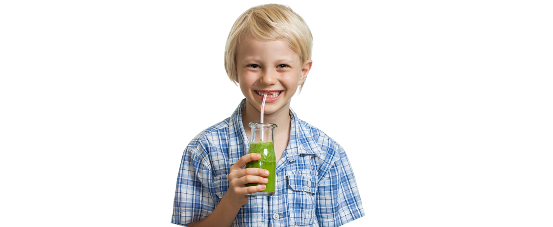 4 Tricks to Sneak Vegetables into Kids' Food | It's tough getting some kids to eat their vegetables, but here are four tricks to sneaking the veggies into your child's food (hopefully without them noticing) | The image shows a boy smiling as he drinks a green smoothie.