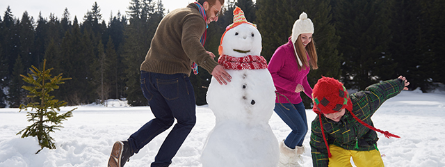 Do You Want to Build a Snowman? | This month's exercise is building a snowman! Bundle up the family, hit the snow, and burn an average of 285 calories an hour. | A family runs around a snowman they just built.