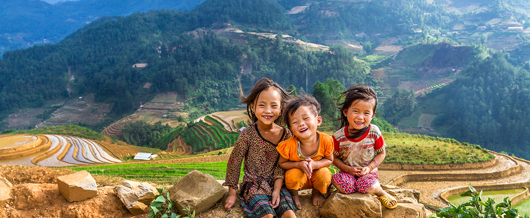 Parenting Around the World | Three children smile for the camera in front of fields in Vietnam.