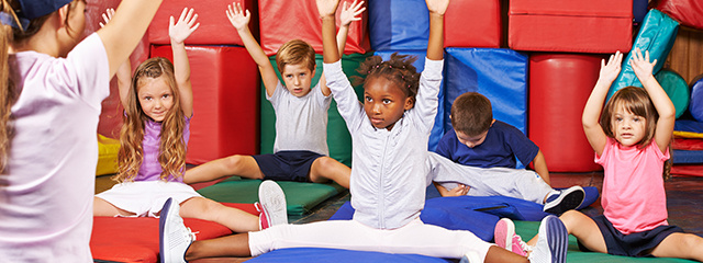 3 Easy Exercises for Kids | Did you know that kids need at least an hour a day of physical activity]? While they might get some of that at recess, try these three exercises with your kids at home to help strengthen their muscles. | A group of kids stretch on colorful mats.