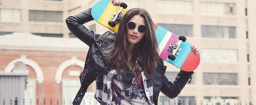 Accepting Your Teen's Personal Style | A teen poses for a photo with her skateboard in a leather jacket, big round sunglasses, flannel and printed shirt.