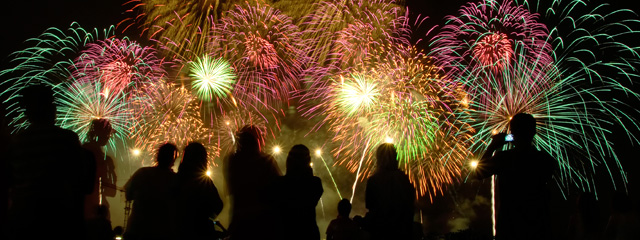 People gather to watch a brilliant, professional-grade fireworks show.