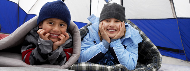 5 Ways to Prep Your Child for Overnight Camp | A boy and girl lay in sleeping bags inside a tent, smiling for the camera.