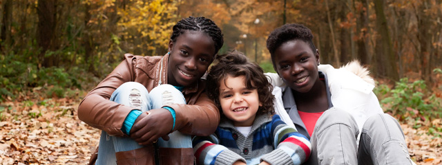 4 Tips for Blending Families   Three kids from a blended family smile for the camera.