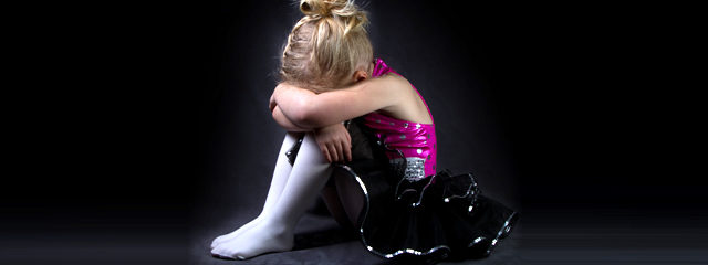 Confronting Fear: Stage Fright | A girl in a dance costume sits on the floor with her head buried in her arms.