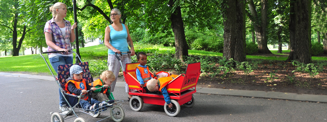 Two women push kids in strollers and talk in the park.