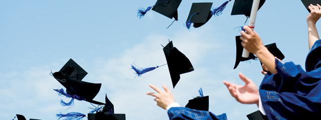 Graduates toss their caps into the air.