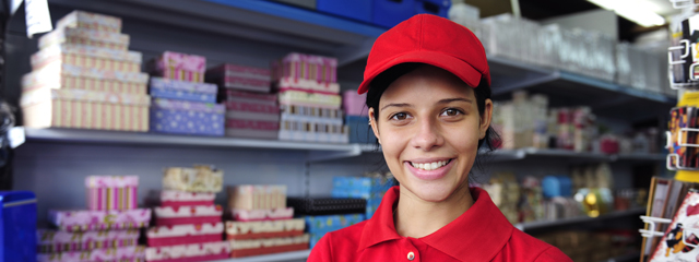 Should Your Teen Have an After-School Job? | A teen wearing a uniform smiles behind the counter at work.