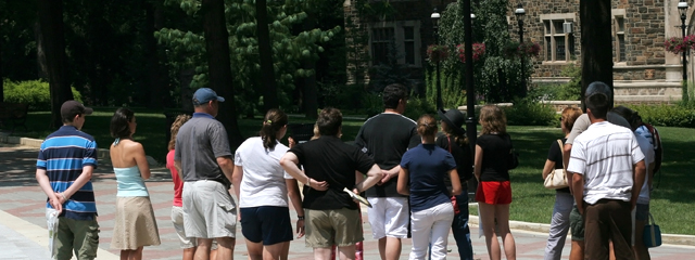 A group of parents and teens participate in a college tour.