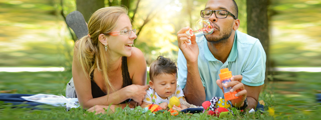 Two parents and their baby sit on a blanket in the park blowing bubbles.