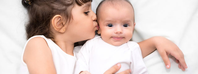 Preparing Your Child for the Arrival of a New Sibling | This mother shares five tips for preparing your child for the arrival of a new sibling. | A girl kisses her baby sister.