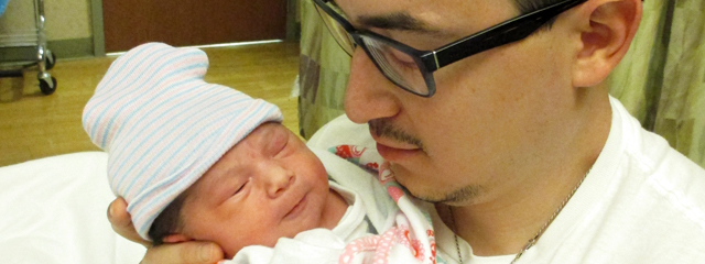 The author holds his newborn daughter in the hospital.