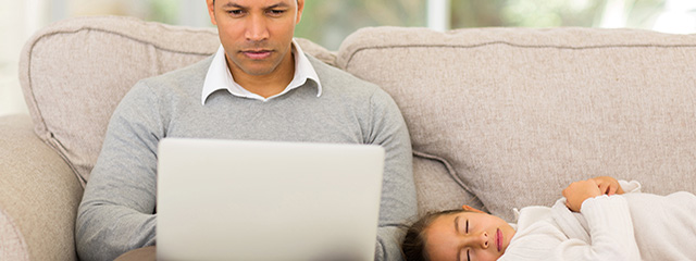 Father's Day for the Modern Dad | This year, avoid the cliché gifts for Father's Day and give dad an experience he really wants based on the type of dad he is. | A dad works from home on his laptop while his daughter naps on the couch next to him.