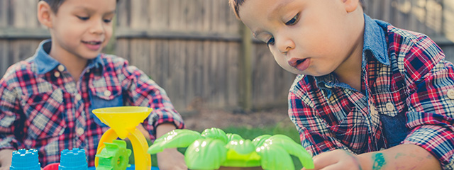 Backyard Summer Learning for Toddlers | Learning opportunities exist right in your backyard! Try these fun activities with your toddler. | A young boy and his brother play with a water toy in the backyard, wearing matching plaid shirts.