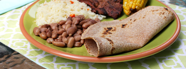 A plate of rice, beans, steak, roasted corn on the cob, and a whole wheat tortilla.