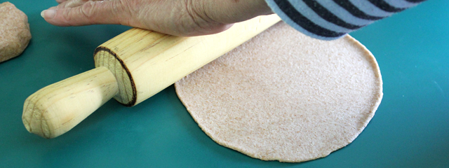 Rolling out the dough with a rolling pin.