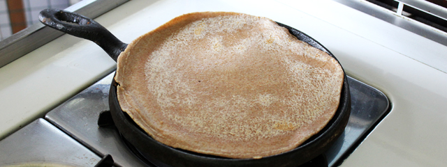 The flattened dough sits on the iron skillet.