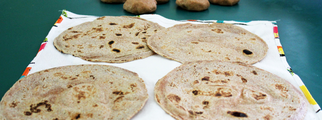 The cooked tortillas sit on a paper towel and cloth napkin to cool.