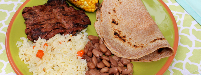 A tortilla sits on a plate with roasted corn, steak, rice, and beans.
