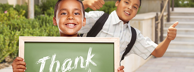 What manners should you be teaching your child now? | A child holds a thank you chalkboard while his friend gives a thumbs up.