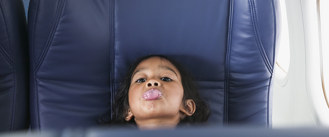 5 Ways to Make Flying with Kids Easier | 5 tips that help traveling with kids on a plane easier for all involved, from the parents to the kids to the other passengers. | A young girl sits on a plane and sticks her tongue out.