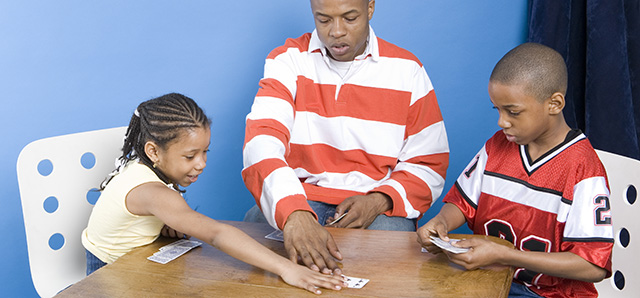 Deal a Royal Flush of Family Fun | Playing card games is a great opportunity for family bonding with kids of all ages. Try it this spring break and see what you learn about your kids. | A photo shows a father playing cards with his daughter and son.