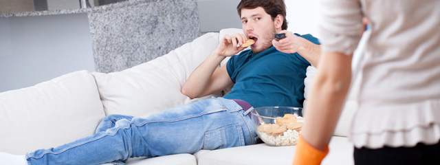 A young 20s son sits on the couch at his parents' house eating chips and watching television.