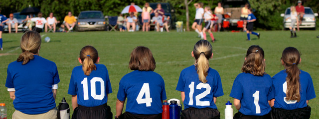 A group of girls sit on a bench while watching their team play soccer.