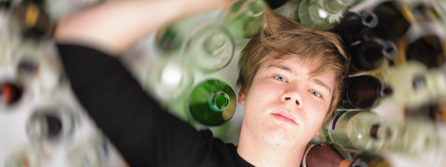 A male teen lays in a blur of glasses and bottles of alcohol.