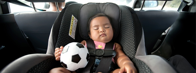 A baby sleeps in the back seat of the car as her parent drives.