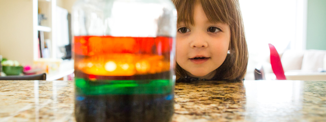 A girl smiles as she looks at the completed experiment.