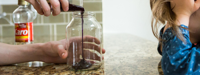 Persona adulta vertiendo colorante en un frasco